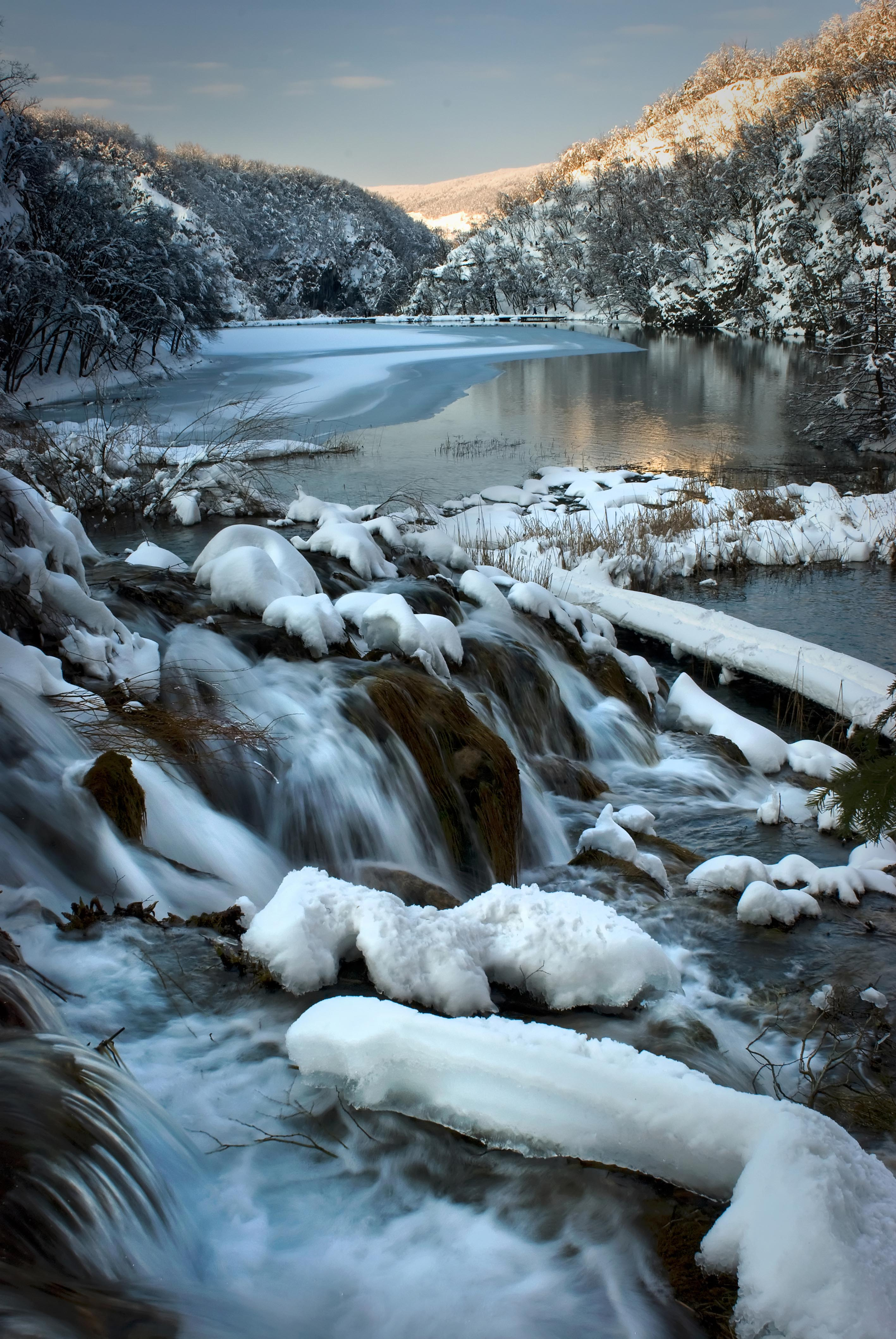 The Plitvice Lakes in winter, frozen waterfalls and the park surrounded by snow.